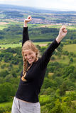 Woman lifts her arms in victory Stock Images