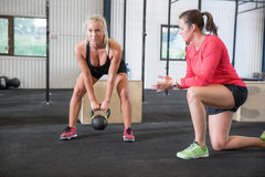 Woman lifts kettlebell with personal trainer Royalty Free Stock Images