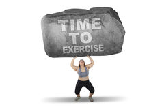 Woman lifts stone with time to exercise word Royalty Free Stock Photography