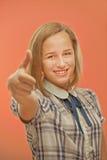 Woman lifts thumb upwards as sign of OK Stock Photos
