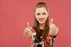 Woman lifts thumbs upwards as sign Royalty Free Stock Images