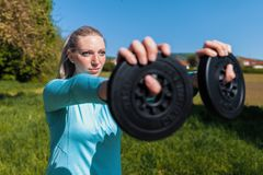 Woman lifts weights in a sport dress royalty free stock image