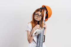 Woman on a light background with glasses holding blueprints, engineer, building, emotions.  Stock Photography