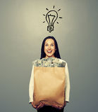 Woman with light bulb and money. Successful young woman with light bulb holding paper bag with money over grey background Royalty Free Stock Photo