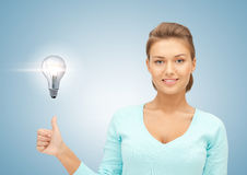 Woman with light bulb showing thumbs up Stock Photography