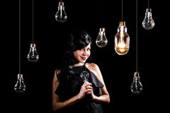 Woman among light bulbs. Beautiful young woman among many light bulbs Stock Photography