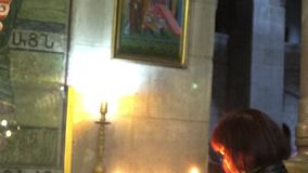 Woman light candles at Jesus tomb stock video
