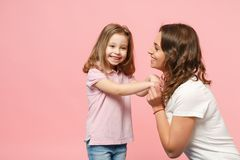 Woman in light clothes have fun with cute child baby girl. Mother, little kid daughter isolated on pastel pink wall. Background, studio portrait. Mother`s Day royalty free stock images