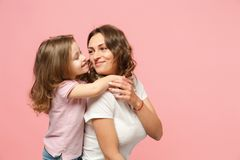 Woman in light clothes have fun with cute child baby girl. Mother, little kid daughter isolated on pastel pink wall. Background, studio portrait. Mother`s Day royalty free stock image