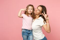 Woman in light clothes have fun with cute child baby girl. Mother, little kid daughter isolated on pastel pink wall stock images