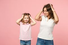 Woman in light clothes have fun with cute child baby girl. Mother, little kid daughter isolated on pastel pink wall. Background, studio portrait. Mother`s Day stock photography
