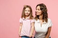Woman in light clothes have fun with cute child baby girl. Mother, little kid daughter isolated on pastel pink wall. Background, studio portrait. Mother`s Day royalty free stock photos