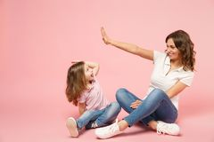 Woman in light clothes have fun with cute child baby girl. Mother, little kid daughter isolated on pastel pink wall royalty free stock images