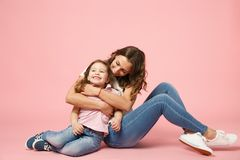 Woman in light clothes have fun with cute child baby girl. Mother, little kid daughter isolated on pastel pink wall. Background, studio portrait. Mother`s Day royalty free stock photography