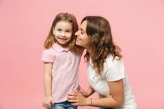 Woman in light clothes have fun with cute child baby girl. Mother, little kid daughter isolated on pastel pink wall. Background, studio portrait. Mother`s Day royalty free stock photo