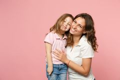 Woman in light clothes have fun with cute child baby girl. Mother, little kid daughter isolated on pastel pink wall. Background, studio portrait. Mother`s Day stock photos