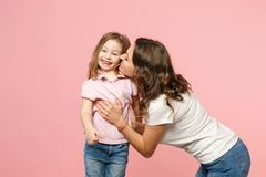 Woman in light clothes have fun with cute child baby girl. Mother, little kid daughter isolated on pastel pink wall. Background, studio portrait. Mother`s Day stock photo