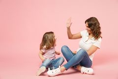 Woman in light clothes have fun with cute child baby girl. Mother, little kid daughter isolated on pastel pink wall. Background, studio portrait. Mother`s Day stock image