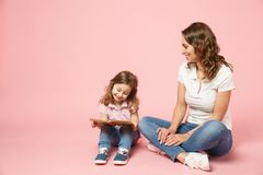 Woman in light clothes have fun read book with child baby girl. Mother, little kid daughter isolated on pastel pink. Background, studio portrait. Mother`s Day royalty free stock images