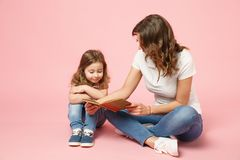 Woman in light clothes have fun read book with child baby girl. Mother, little kid daughter isolated on pastel pink. Background, studio portrait. Mother`s Day royalty free stock photography