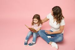 Woman in light clothes have fun read book with child baby girl. Mother, little kid daughter isolated on pastel pink. Background, studio portrait. Mother`s Day royalty free stock image