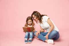 Woman in light clothes have fun read book with child baby girl. Mother, little kid daughter isolated on pastel pink stock images