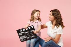 Woman in light clothes hold clapperboard, child baby girl. Mother, little kid daughter isolated on pastel pink wall. Background, studio portrait. Mother`s Day royalty free stock photos