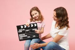 Woman in light clothes hold clapperboard, child baby girl. Mother, little kid daughter isolated on pastel pink wall royalty free stock image