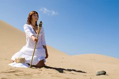 Woman with light in the desert. Wearing white dress Royalty Free Stock Photo