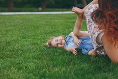 Woman in light dress and smiling little cute child baby girl lie on green grass in park rest play and have fun. Mother. Little kid daughter. Mother`s Day, love royalty free stock photo