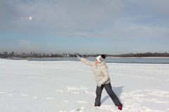 The woman in a light jacket throwing a snowball on the riverbank Royalty Free Stock Photo
