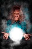 Woman with light sphere between her palms, spiritual energy. Young beautiful woman with long golden hair, dressed in blue clothes making some magic. She is Royalty Free Stock Photography