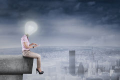 Woman with lightbulb head using tablet Royalty Free Stock Photo