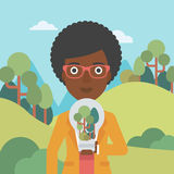 Woman with lightbulb and trees inside. Stock Image