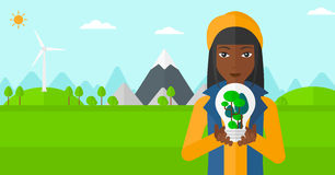 Woman with lightbulb and trees inside. Royalty Free Stock Photography