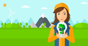 Woman with lightbulb and trees inside. Stock Photography