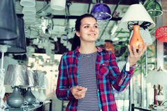 Woman in lighter shop is choosing stylish and modern lamp Stock Photo