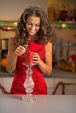 Woman lighting candle in decorated kitchen Royalty Free Stock Photography