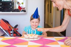 Woman lighting candles on birthday cake and child looking laughing. Woman lighting candles with lighter in hand on birthday cake on colorful tablecloth at home stock images