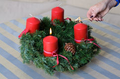 Woman lighting candles on a Christmas wreath Royalty Free Stock Image