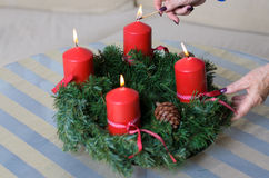 Woman lighting candles on a Christmas wreath Stock Photo