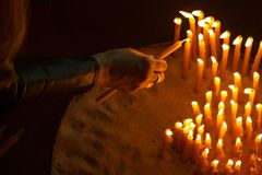 Woman lighting candles in a church Stock Photos