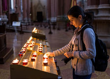 Woman lighting candles in church Stock Photos