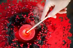 Woman lighting a Christmas candle with red decoration, hand and smoke on the background. Chrismas New Year layout concept. Top stock photo