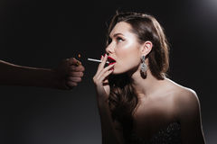 Woman lighting cigarette stock images