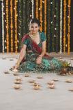 Woman lighting oil lamps on Diwali Stock Image