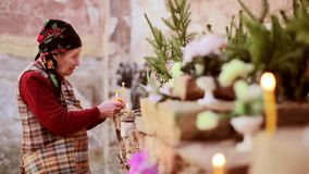 Woman lighting prayer candle in a abandoned church stock footage