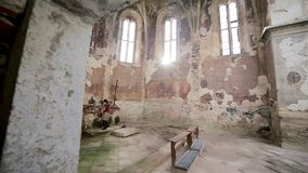 Woman lighting prayer candle in a abandoned church stock video