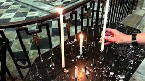 Woman lighting prayer candle aka offering, sacrificial or memorial candles in a church stock footage