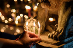 Woman lighting prayer candle in temple Stock Images